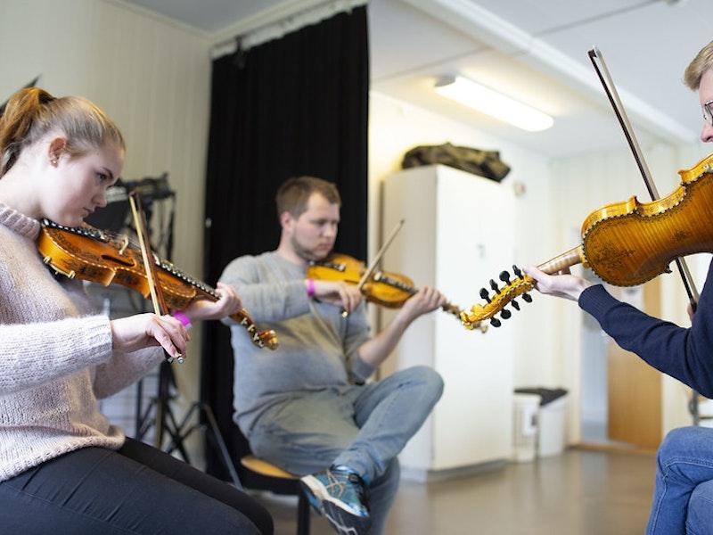 Tre personer spiler fiolin.