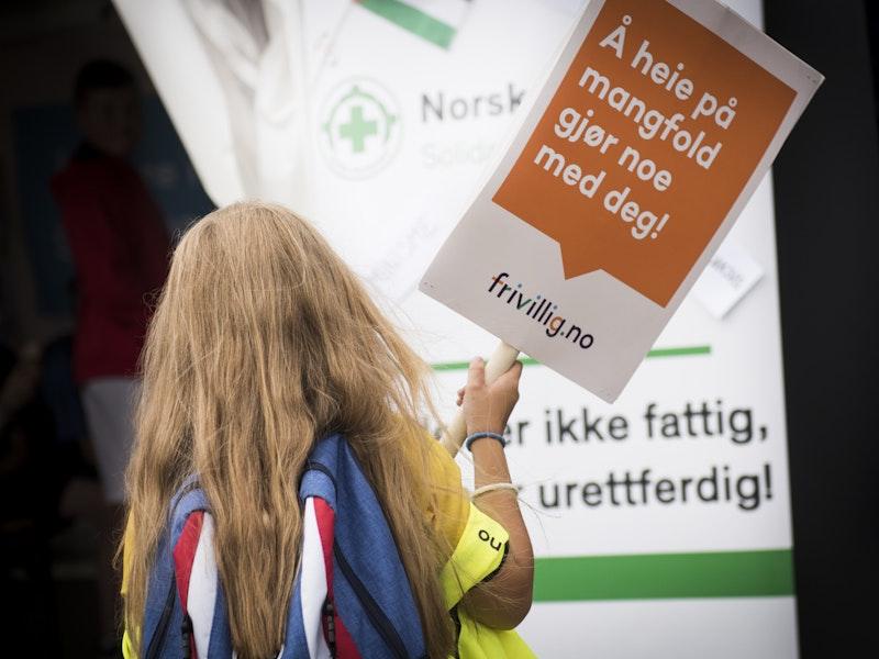 """Jente holder Frivillig.no-skilt med teksten """"Å heie på mangfold gjør noe med deg"""""""
