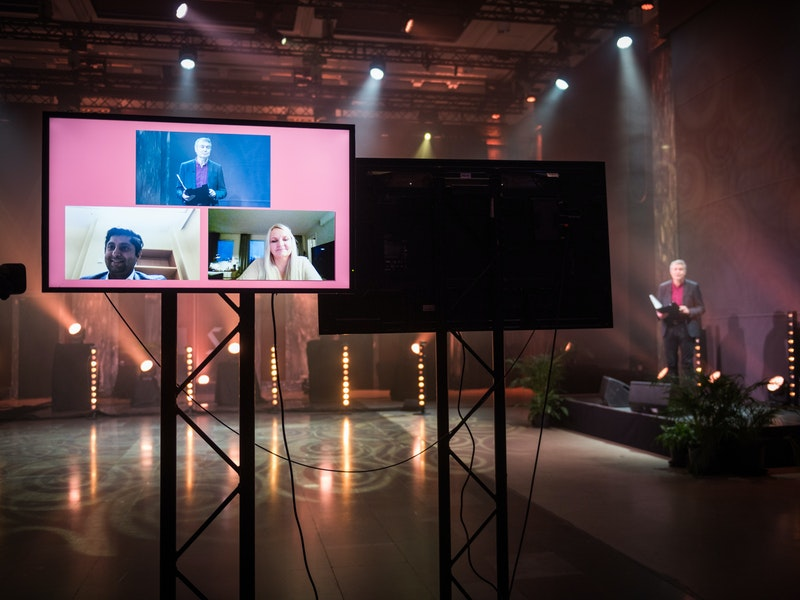 Bilde av tre personer på skjerm i forgrunnen og en av de i bakgrunnen.