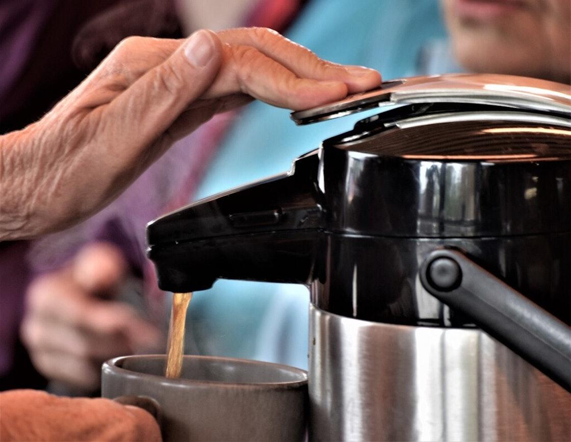 Hånd som trykker på pumpen på en kaffekanne