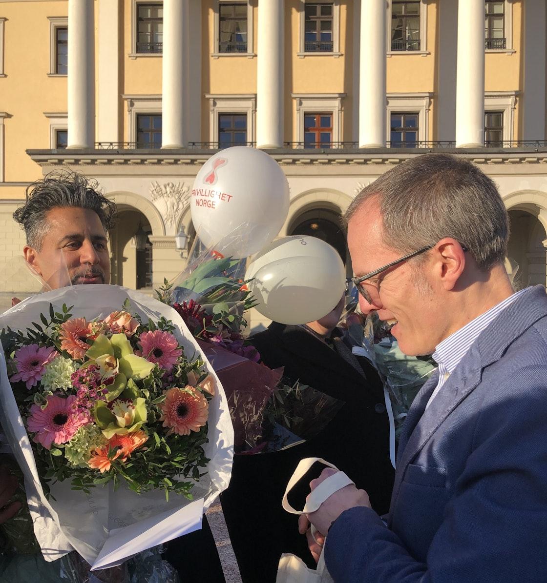 Stian Slotterøy Johnsen overrekker blomster til Abid Raja på slottsplassen