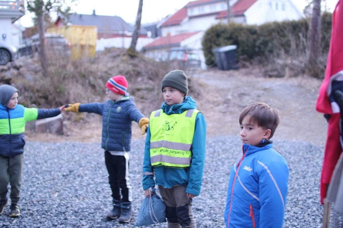 fire barn står ute med en meter avstand som de måler med armene.