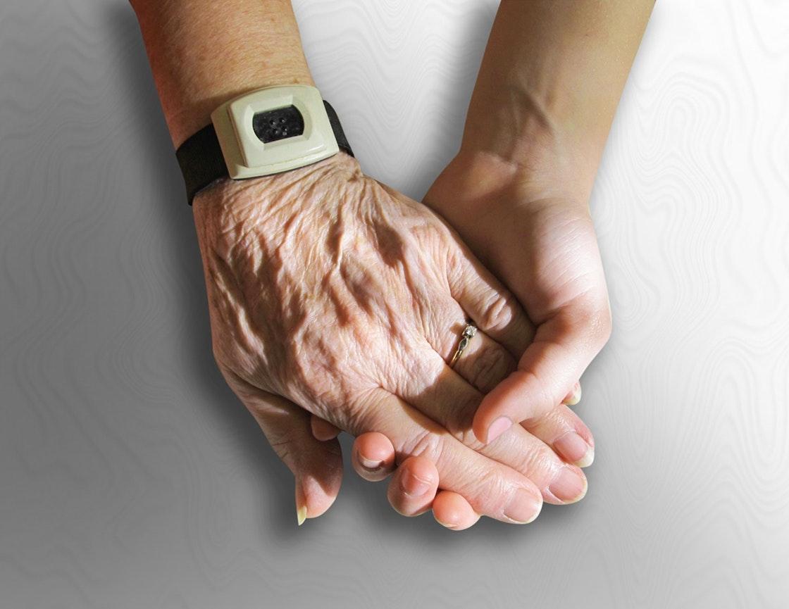 En eldre og yngre person holder hender. Nærbilde av hendene.