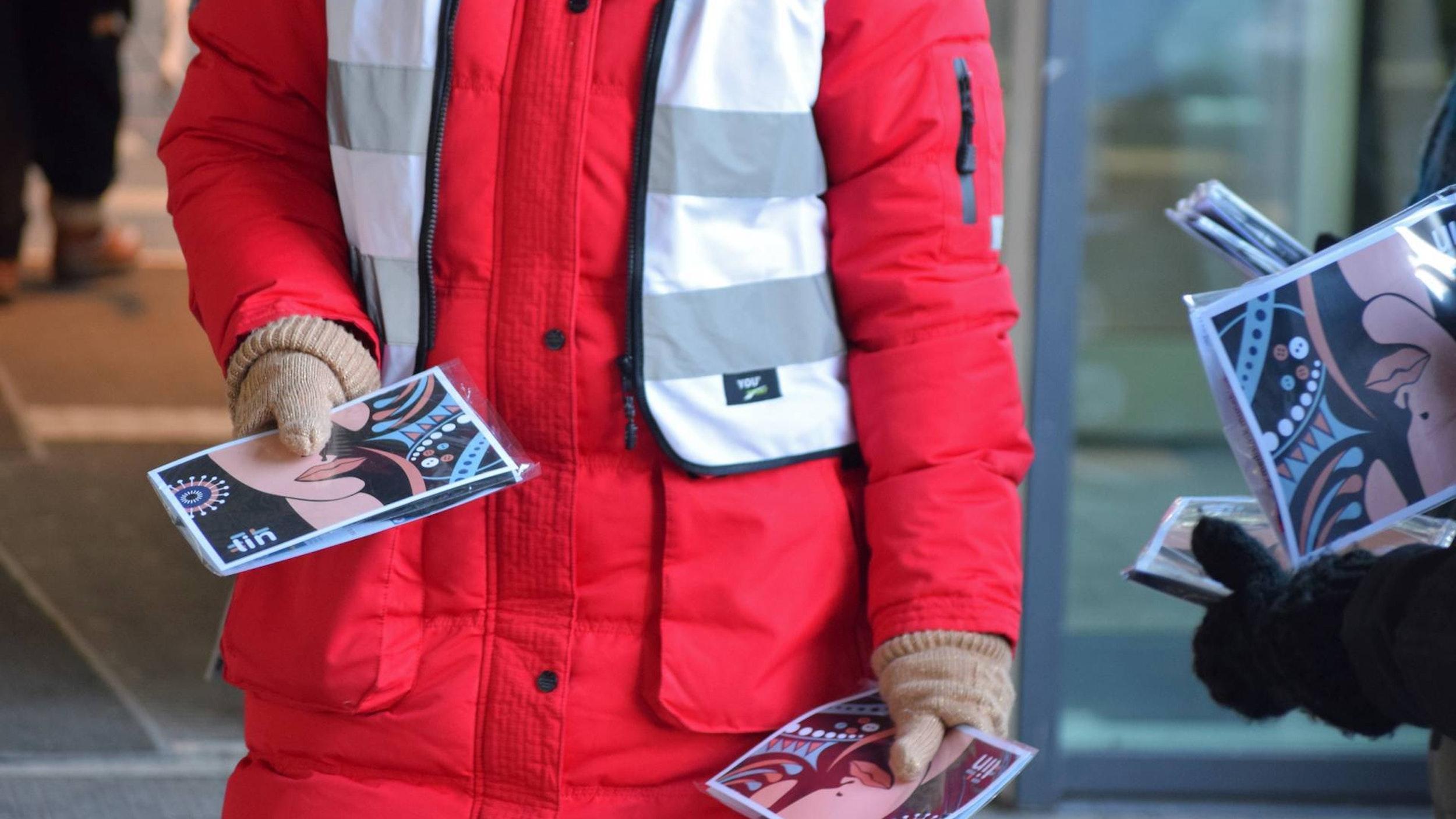 Bilde av person i rød jakke som deler ut en brosjyre.