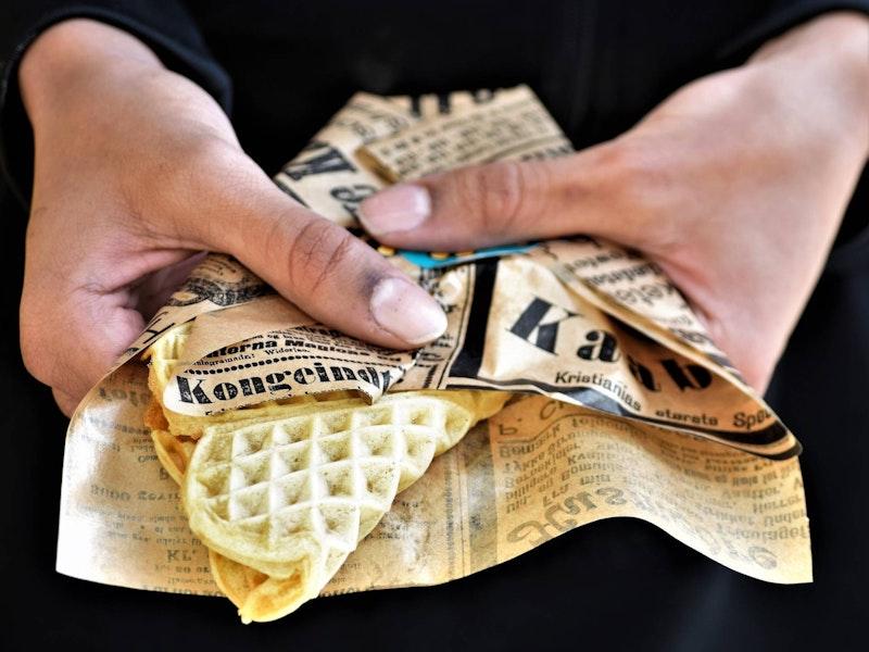Hender som holder vaffel pakket inn i avispapir