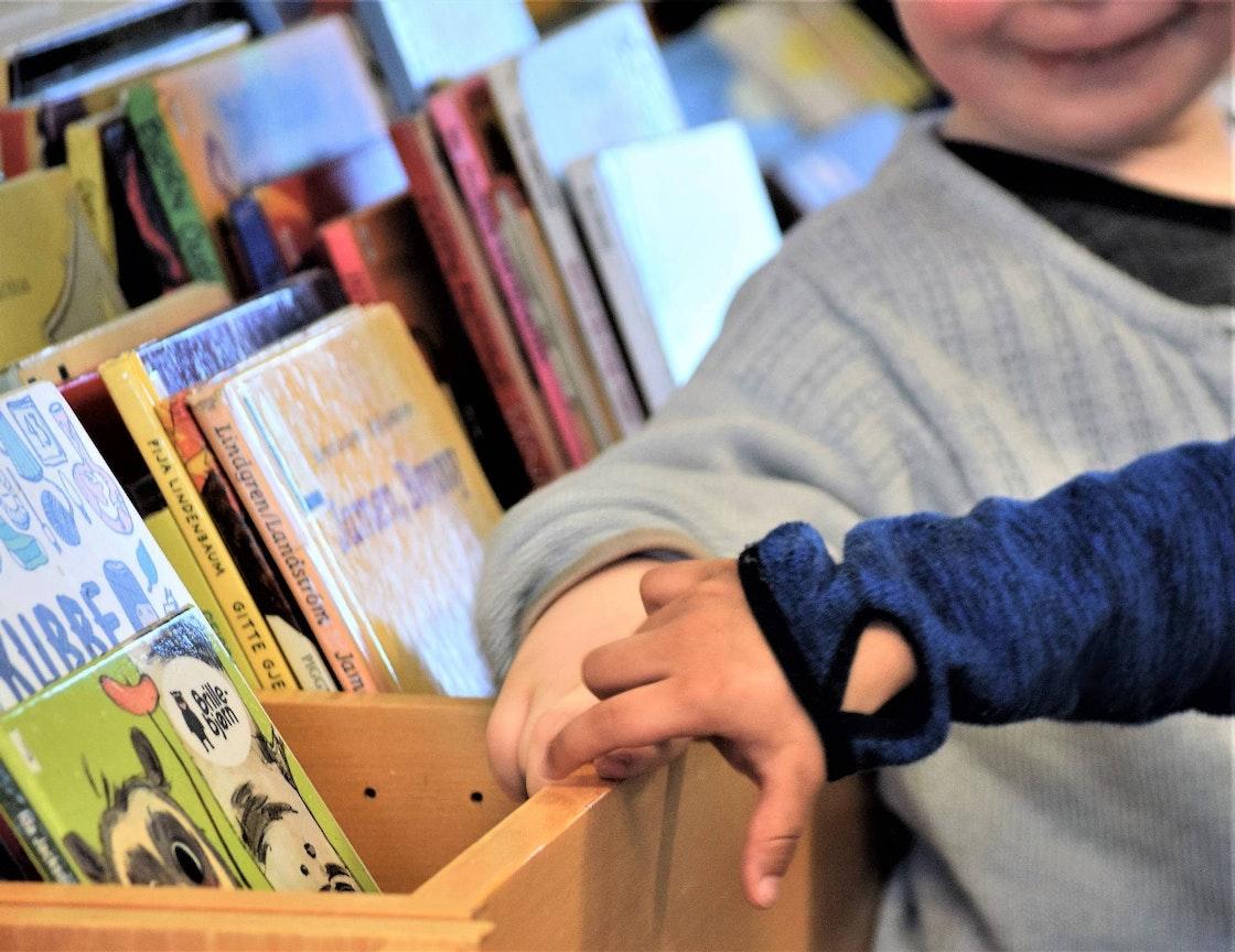 hendene til to barn foran kasse med bøker.