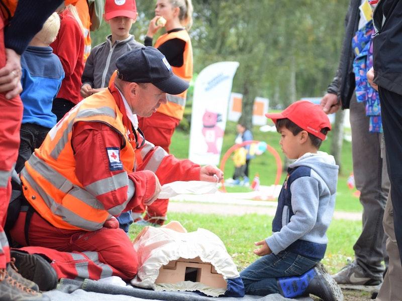 Mann i refleksvest viser gutt førstehjelp