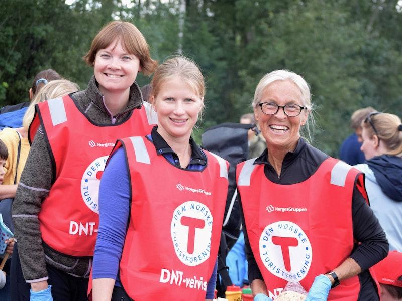 Tre kvinner i rød vest med logoen til Den Norske Turistforeningen smiler til kamera.