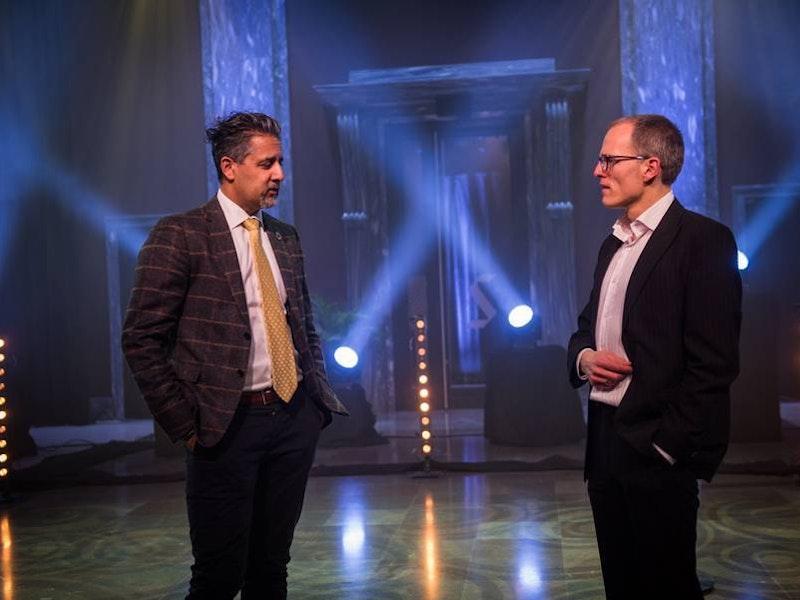 Abid Raja og Stian Slotterøy Johnsen samtaler på en scene med lyskastere i bakgrunnen