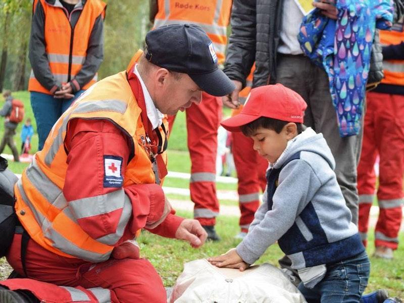 En voksen mann med Røde Kors-uniform viser et gutt hjertekompressjoner.