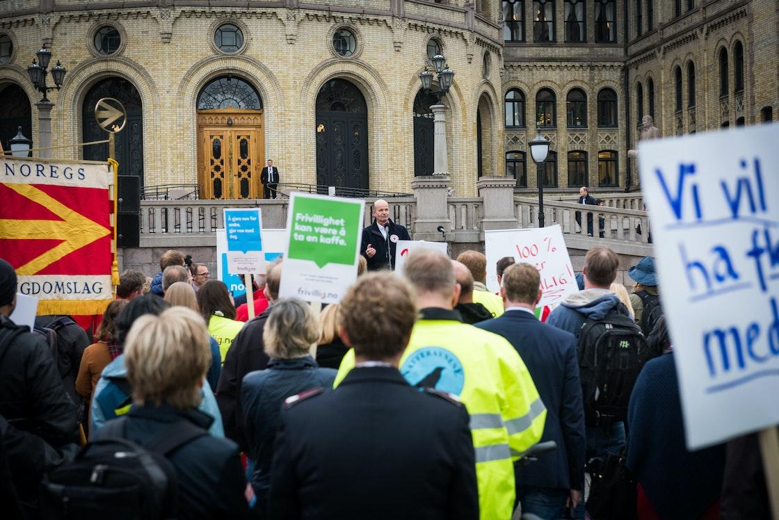 Bilde av personer som demonstrerer for full momskompensasjon med plakater foran Stortinget.