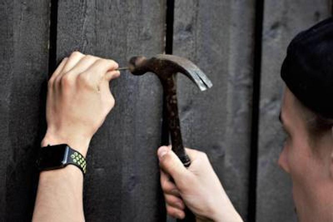 En mann setter en spiker ri en vegg